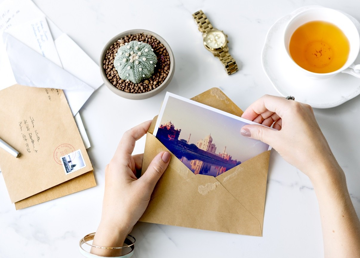 woman opening direct mail postcard - does postcard marketing work